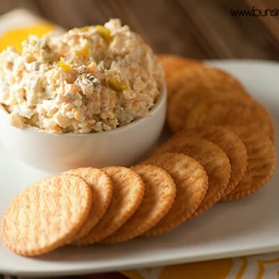 A plate of crackers with a cup of cheese spread.
