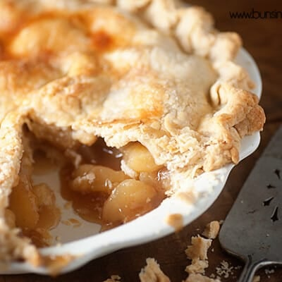 A close up of a peach pie with a slice removed.