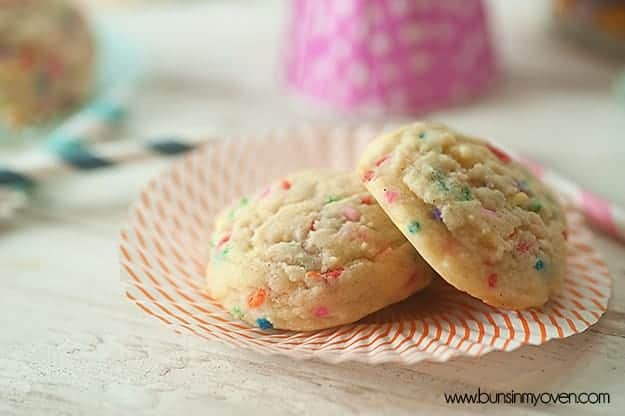 A close up of a couple of confetti sugar cookies on a paper plate.