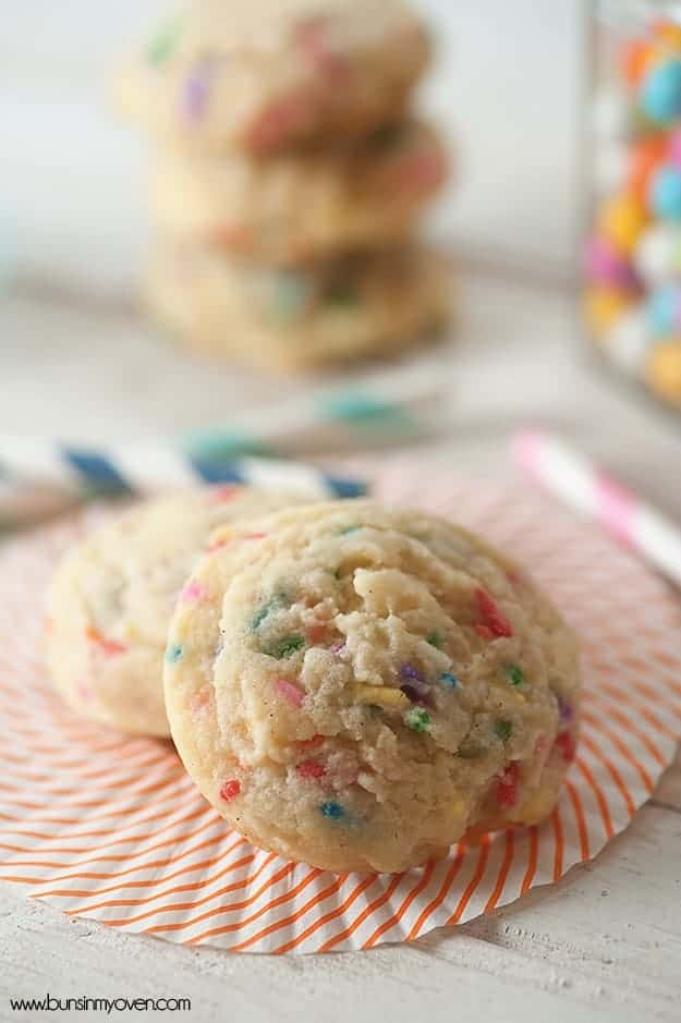 Two sugar cookies on a paper napkin with colorful straws surrounding it.