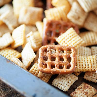 A close up of Chex cereal and a rectangle pretzel on a baking sheet.