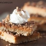 Two pumpkin pie bars topped with whipped cream.