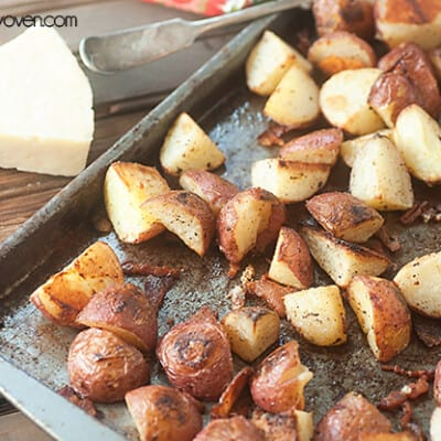 A close up of roasted potatoes in a baking sheet on a table.