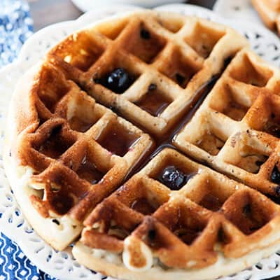 A blueberry waffle on a decorative white plate.