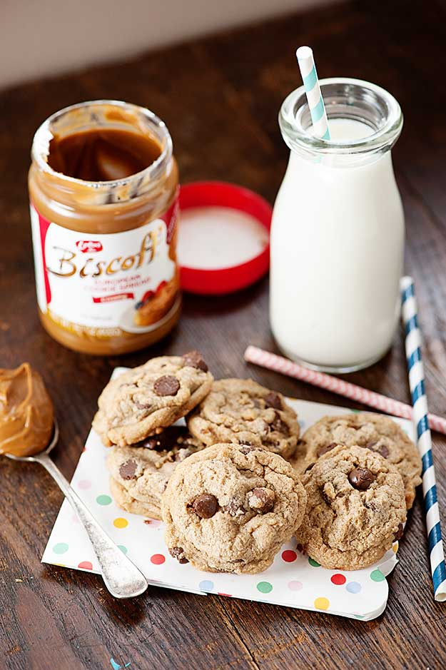 A jar of biscoff and a jar of milk on a table with a plate of chocolate chip cookies.