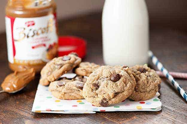 A few chocolate chip cookies on a folded cloth napkin in front of a jar of milk.