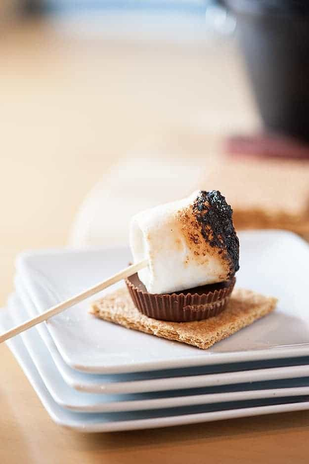 A toasted marshmallow and a peanut butter cup on top of a graham cracker.