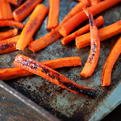 A bunch of sliced carrots on a baking sheet.