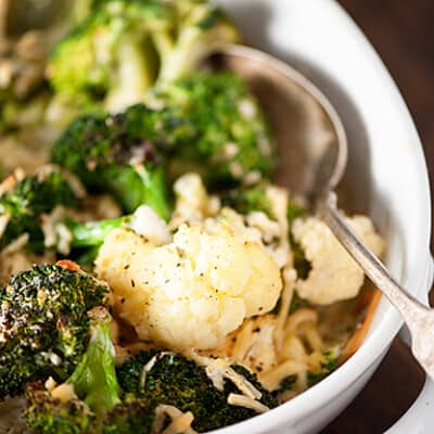 Cauliflower and broccoli in a white bowl with a silver spoon.