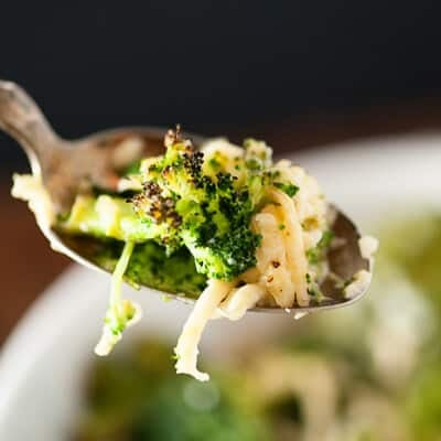 Broccoli and cheese on a spoon being held up to the camera.