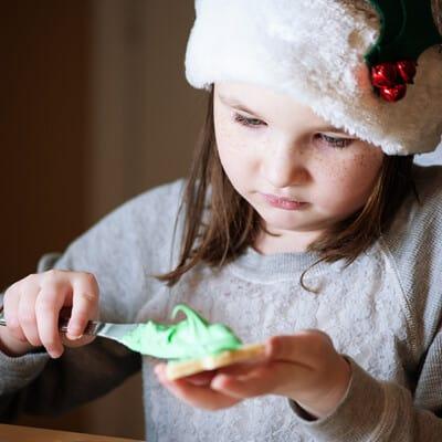 A girl buttering bread in a santa hat.