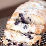 A loaf of blueberry muffin bread cut into slices on a wire cooling rack.