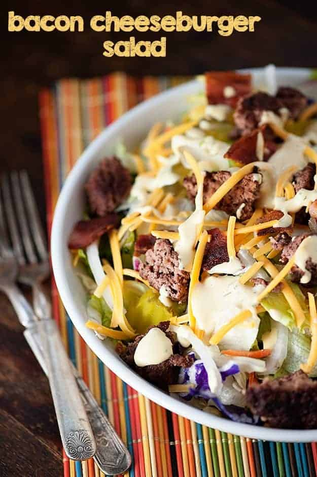 A white bowl of salad topped with bacon and shredded cheese on a striped cloth napkin.