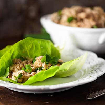 A large lettuce wrap with Asian chicken in the middle.