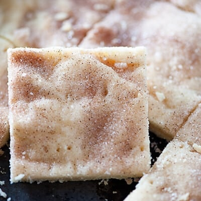 A close up of a square of shortbread cut out of a baking sheet full of shortbread.