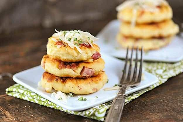 Three stacked up mini potato pancakes on a square plate.