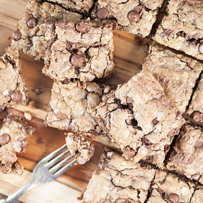Several oatmeal cookie bars spread out over a cutting board.