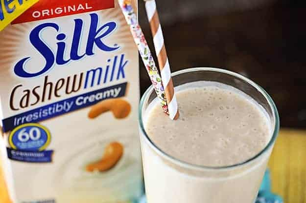 A glass of peanut butter smoothie next to a container of silk milk.
