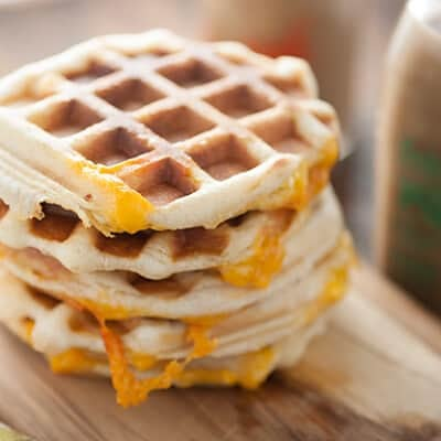 A stack of waffles with cheese in between them.