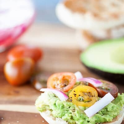 These English muffins are topped with smashed avocados, pickled onions, and cherry tomatoes for a quick breakfast or snack recipe that is filling and satisfying!