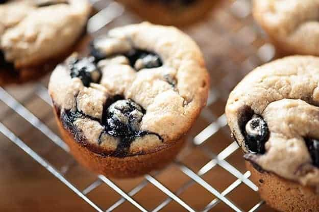 A close up of blueberry muffins on a wire cooling rack.