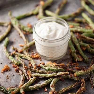 Parmesan coated green beans on a baking sheet with a jar of white dipping sauce.