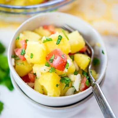 Mexican potato salad in stacked white bowls.