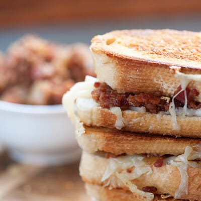 A close up of a few stacked up bacon jam sandwiches.