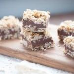 No bake chocolate bars stacked on a narrow cutting board.