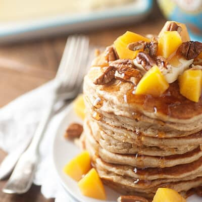 A stack of pancakes topped with peach chunks and pecans.
