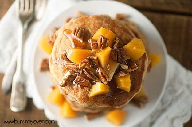 Overhead view of pecans, syrup, and peaches on a stack of pancakes.