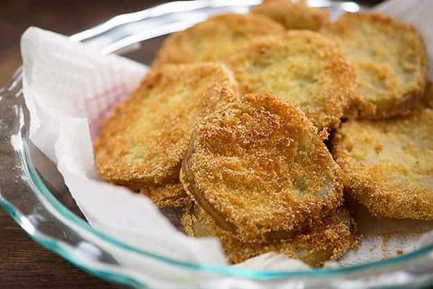 A clear glass pie plate lined with a paper towel with a pile of fried green tomatoes in it.
