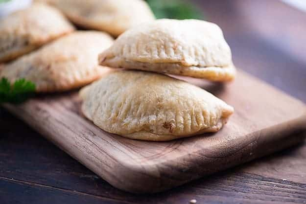 A close up of a couple of empanadas stacked on a narrow wooden cutting board.