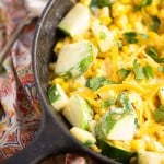 Close up of a cast-iron skillet with shredded cheese, corn, and zucchini.