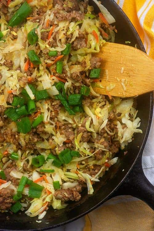 stirring egg roll ingredients in a skillet