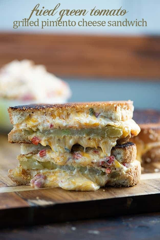 Two stacked halves of grilled tomato and cheese sandwich.