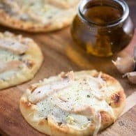 Homemade spicy garlic oil spread on a cheesy chicken flatbread! Such a quick and easy weeknight dinner!