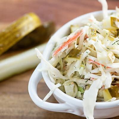 Close up of a bowl of cole slaw on a wooden cutting board in front of pickle spears.