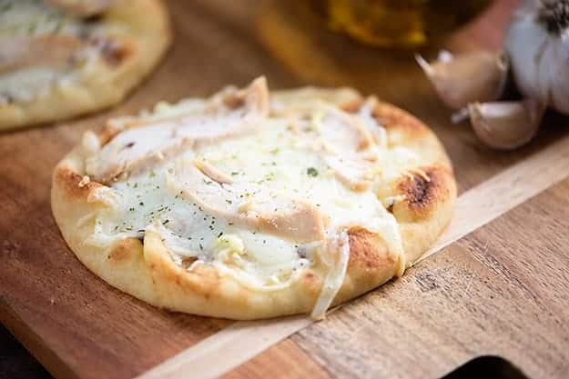 Chicken topped flatbread on a cutting board.