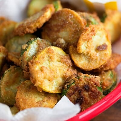 Fried zucchini slices stacked on top of each other in a red appetizer tray.