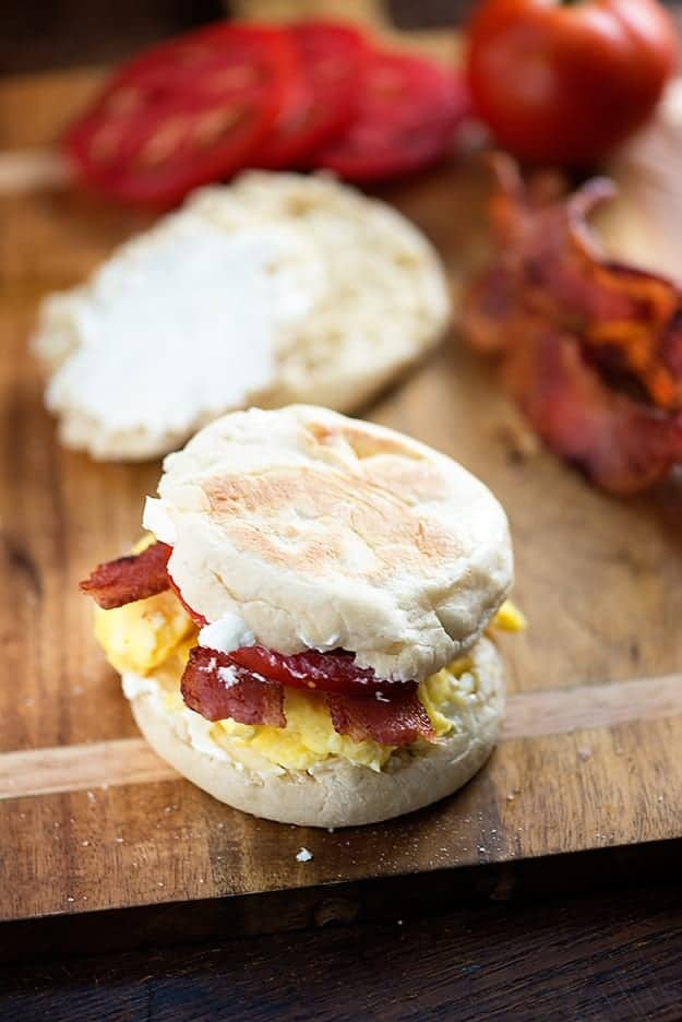 A BLT on an English muffin on a wooden cutting board