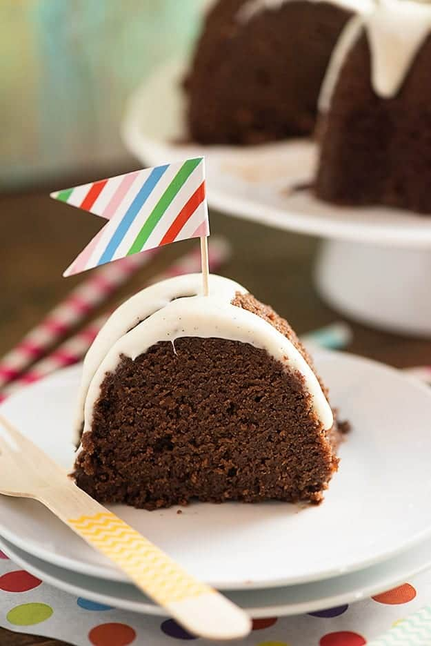 A close up of a piece of chocolate cake on a plate with a tiny colorful flag in it.