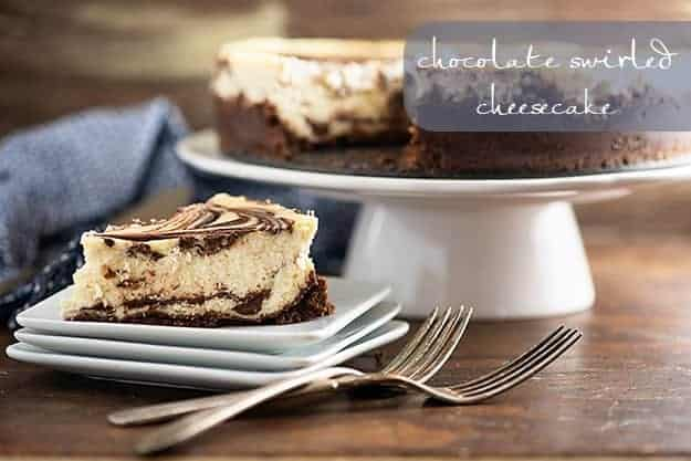 A piece of chocolate swirl cheesecake on a square plate in front of a cheesecake on a cake stand.