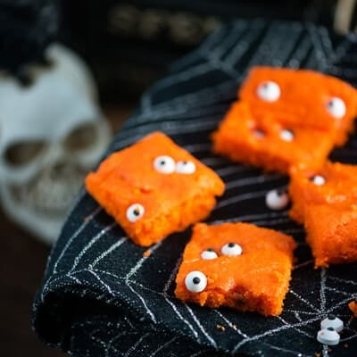 Small orange cake bars with candy eyeballs on a black cloth napkin