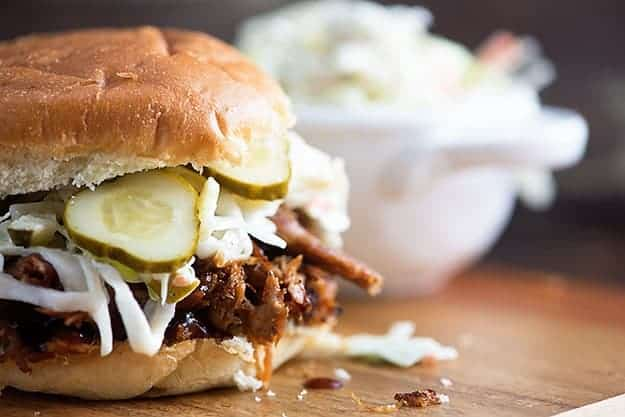 Slow cooker pulled pork made in the crock pot! Perfect for these easy sandwiches with dill pickle slaw and homemade barbecue sauce! This is one of our favorite recipes!