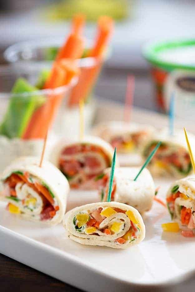 Many tortilla roll-ups on a white appetizer tray.