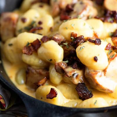 A cast-iron skillet with cheesy gnocchi and bacon in it.