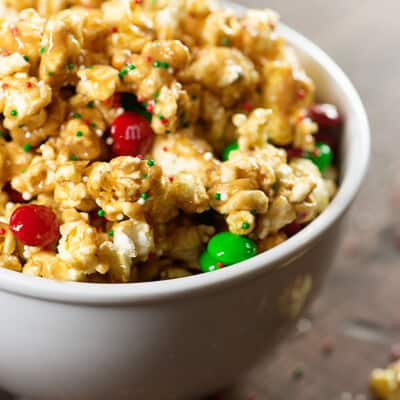 A bowl of popcorn with red and white M&M's in it.