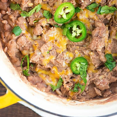 A large pot full of refried beans with jalapenos.