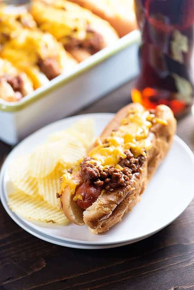 A sloppy joe hot dog on a plate with some rippled potato chips.